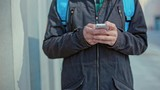 Close Up on Male Hands Type on Phone He is Standing Against the Gray of the House Outdoors on Cold Day