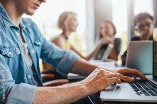 Poszter Young man using laptop with classmates studying in background