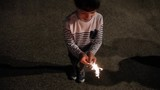 Top view of happy kid standing while holding sparkler outdoors in the night