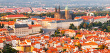 Prague Castle complex with gothic St Vitus Cathedral in the evening time illuminated by sunset, Hradcany, Prague, Czech Republic. UNESCO World Heritage. Panoramic aerial shot from Petrin Tower.
