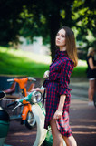 Fashion woman in checkered dress posing and pulling her hair near scooter over summer park background
