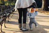 Mom teaching her son's first baby steps in the park - 128347948
