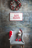 Beautiful Christmas wreath and a chair with a Santa hat with wishing happy holidays