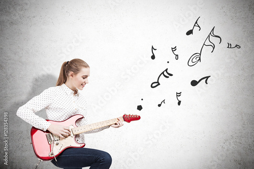 Poster Woman with an electric guitar near a concrete wall with note ske