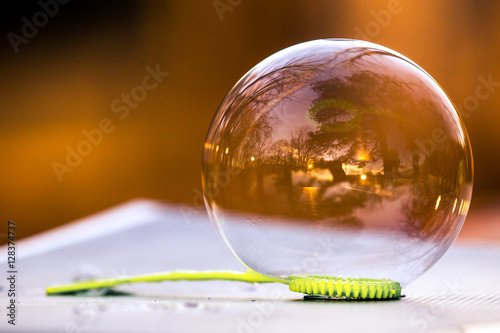 Poster Soap bubble on wand lying on surface, showing round, angled, and straight shapes