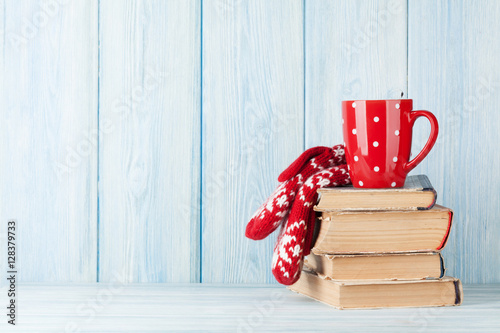 Hot chocolate cup and mittens over books