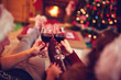 couple with red wine, against xmas tree and fireplace