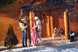 family decorate his wooden house for Christmas