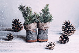 Vintage Christmas composition - new year holiday toy for christmas tree - shoes boots, cones and fir branches on wooden background. Free place for text, copy space. Snow time