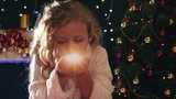 Cute girl fairy blowing magical glitter at christmas night.