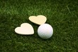 Gift for golfer, Golf ball with two wooden heart shape on green grass course