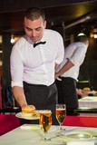 Waiter serving burger and beer on a table