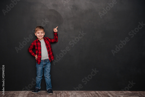 Fotografiet Cute little boy standing over chalkboard and pointing up