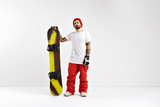 Cool rider in plain white t-shirt, red snowboard pants and red beanie holding a snowboard isolated on white
