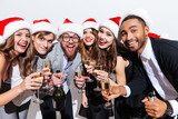 People in santa hats celebrating new year and drinking champagne