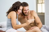 Happy couple looking at pregnancy test on bed