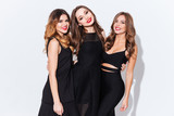 Three happy attractive young women in black dresses standing together