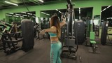 Strong woman doing exercise on training apparatus in gym