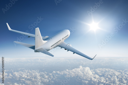 Airliner flying towards the sun in blue sky