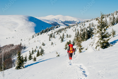 Poster A tourist in a red clothes with a backpack travels high winter C