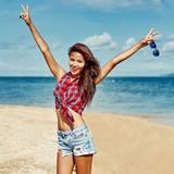 Pretty girl having fun on a summer beach with arms raised