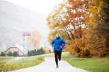 Young handsome hipster athlete running against colorful autumn n