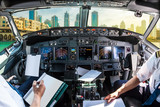 Airplane cockpit flying on Dubai skyscrapers skyline, United Arab Emirates, with pilots arms and blank white papers for copy space.