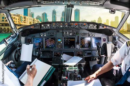 Poster Airplane cockpit flying on Dubai skyscrapers skyline, United Arab Emirates, with pilots arms and blank white papers for copy space