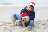 kid with his dog with santa claus hats in the beach