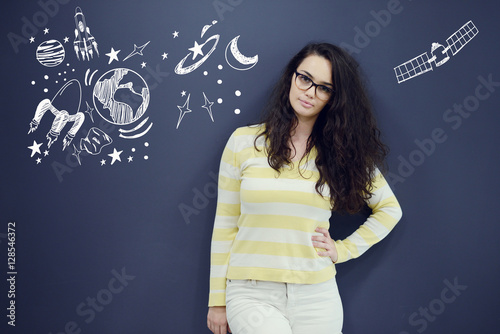 Poster Young thinkful woman on blue gray background with universum icons