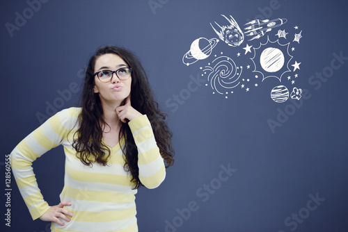 Young thinkful woman on blue gray background with universum icons Poster