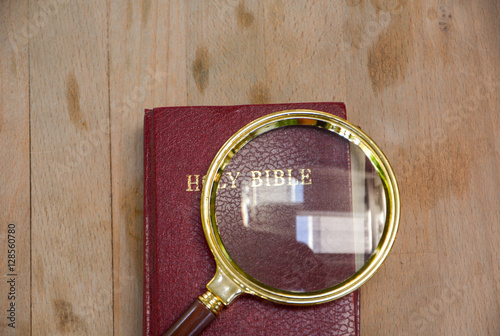 bible book and magnifying glass on wood background Poster