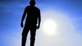 Silhouette of man standing and stretching arms up in front of blue sky on sunny day.