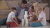 Parents and their little kids building a tower of toy bricks, son hesitating and mom helping him to put a brick on the top