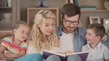 Parents and their little kids sitting on couch and looking at the book on dads laps, mom explaining something interesting to children