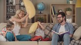 Husband relaxing and reading a book in the living room while his wife and little kids   hitting him with sofa cushions playfully, smiling and giggling