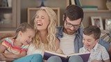 Parents and their little kids sitting together on couch and looking at the book, mom pointing at something funny, kids laughing happily