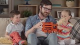Father playing with a truck toy with two kids, daughter participating and son watching