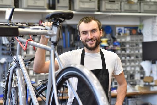 Deurstickers freundlicher Zweiradmechnaiker in einer Fahrradwerkstatt repariert Räder