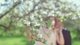 Beautiful bride and groom in a vintage wedding dress posing in a blooming apple garden. Spring mood. Young woman in a white vintage dress