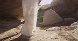 Girl walking in the desert through the rocks and caves. Mojave desert views. Slow motion