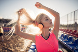 sport outdoor photo of beautiful young blonde woman in pink colorful suit listening to music on headphones by the beach