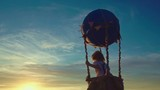 Boy in a balloons at sunset