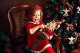 Cheerful little girl in Christmas outfit sitting in old chair holding decorative Santa and looking at camera.