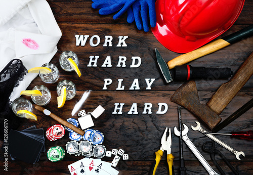Poster Work hard play hard written with letters on the wooden table and objects which represent the popular phrase as lifestyle concept