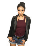 Beautiful latina girl wearing denim short shorts, burgundy top, hair pulled back, sporting a black choker while holding leather jacket behind her. Fun,flirty, Spring casual West Coast look.