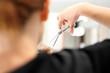 Strzyżenie włosów. Fryzjer strzyże kobietę w salonie fryzjerskim