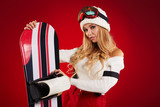 Woman with a snowboard, studio shoot. red background