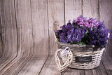 Lavanda en cesta de mimbre blanca y corazón sobre fondo de madera.