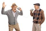 Cheerful seniors telling jokes to each other through tin can phone